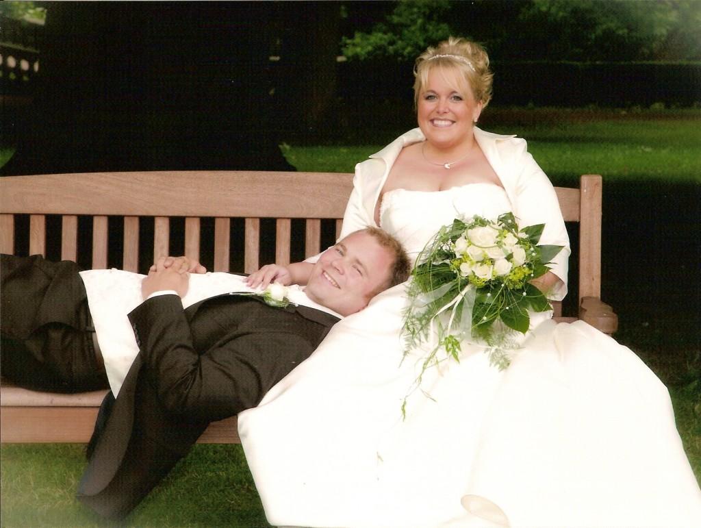 Glückliches Brautpaar auf einer Bank